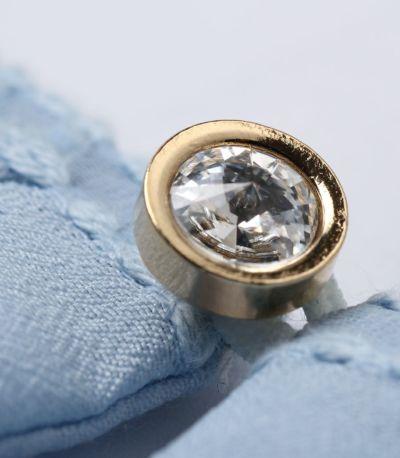 ゴールドの淵にダイヤモンドカット風のクリアなボタンが、ネックのワンポイントに。