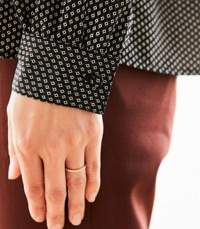 袖口のカフスが手首を華奢に演出。ちらりと見えるくるみボタンがおしゃれ。