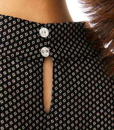 バックスタイルの華やかなボタンはスワロフスキー・クリスタル/Swarovski Crystals使用。