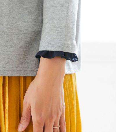 着まわしの効くバランスの良い8分袖に、涙あきのボタンと同色の、さりげないフリル。